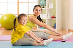 Child girl and her mother doing gym exercise at home Royalty Free Stock Photo