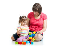 Child girl and her mother play with building blocks Royalty Free Stock Image