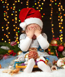 Child girl hide face in christmas decoration, happy emotions, winter holiday concept, dark background with illumination and boke l Stock Photo