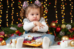Child girl hides her toys, portrait in christmas decoration, winter holiday concept, dark background with illumination and boke li Royalty Free Stock Image