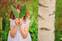 Child girl hiding behind green leaves in summer forest Royalty Free Stock Photography