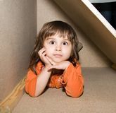 Child girl hiding in wooden box, dreams alone Royalty Free Stock Image