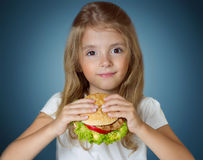 Child girl holding hamburger. Kid with fastfood sandwich. royalty free stock photos