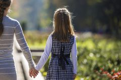 Child girl holding mother hand on warm day outdoors on sunny bokeh background. Family relationship and recreation.  royalty free stock photo