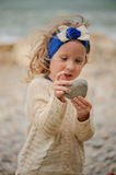 Child girl holding stone with focus on hands Royalty Free Stock Image