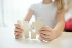 Child girl holding  two big wooden puzzle pieces. Hands connecting jigsaw puzzle. Close up photo with small dof Stock Photo