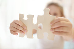 Child girl holding  two big wooden puzzle pieces. Hands connecting jigsaw puzzle. Close up photo with small dof Royalty Free Stock Photography