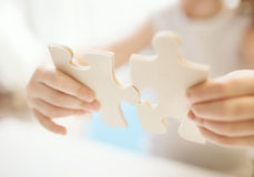 Child girl holding  two big wooden puzzle pieces. Hands connecting jigsaw puzzle. Close up photo with small dof Stock Image