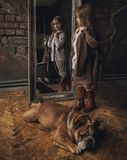 Child girl in image of Sherlock Holmes stands next to English bulldog and looks at mirror reflection on background of old interior. Child girl in image of Royalty Free Stock Photo