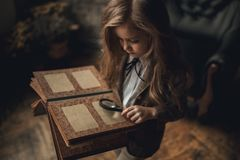 Child girl in image of Sherlock Holmes stands in room and looks photoalbum with magnifier on background of old interior. Closeup. Child girl in image of Stock Images