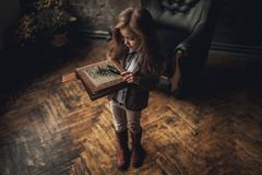 Child girl in image of Sherlock Holmes stands in room and looks photoalbum with magnifier on background of old interior. Closeup. Child girl in image of Stock Image