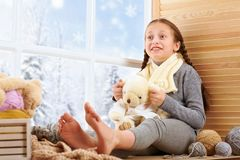 Free Child Girl Is Sitting On A Window Sill And Playing With Bear Toy. Beautiful View Outside The Window - Sunny Day In Winter And Snow Royalty Free Stock Photography - 134805067