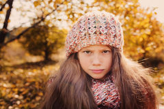 Child girl in knitted scarf and sweater on autumn walk in forest Stock Photo