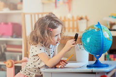 Child girl learning with globe at home. Preschooler child girl learning with globe and loupe at home Royalty Free Stock Image