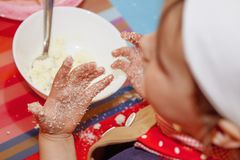 Child girl is learning how to make a cake. Humorous photo. Selec. Tive focus on the hands Stock Images