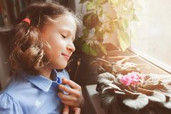 Child girl learning to grow potted plants at home, Kid exploring home flowers  with loupe. Nature care and ecology concept Stock Images
