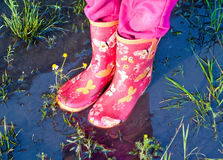 Child girl legs in pink galoshes inside puddle of water. Child girl legs in pink galoshes standing inside a puddle of water - rainy summer holiday concept Stock Image