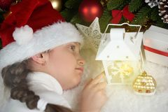 Child girl lie with candle lantern and dream, christmas decorati Stock Image