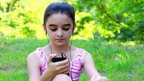 Child girl listening to music on a smartphone stock footage