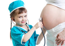 Child girl listening to pregnant mother's belly Stock Images