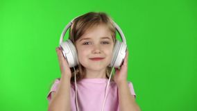 Child girl listens to music through the headphones. Green screen. Slow motion stock video footage