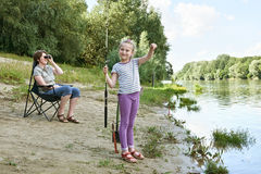 Child girl look on caught fish, people camping and fishing, family active in nature, river and forest, summer season Royalty Free Stock Photos
