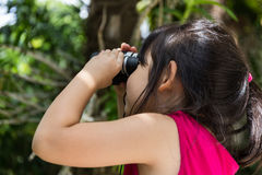 Child, Girl, Looking Through Binoculars. Cute girl is looking through binoculars during a trip Stock Photo