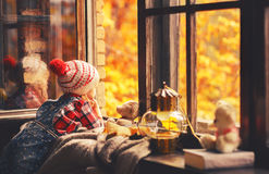 Child girl looking through open window at nature autumn Stock Image