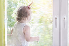 Child girl looking out window. Kid looks out window Stock Images