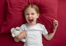 Child girl lying on the bed refuses to sleep stock images