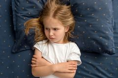 Child girl lying on the bed refuses to sleep royalty free stock images