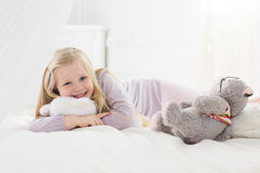 Child girl lying in bed with teddy bear Stock Images