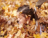 Child girl is lying and playing in fallen leaves in autumn city park stock image