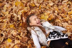 Child girl is lying and playing in fallen leaves in autumn city park stock photography