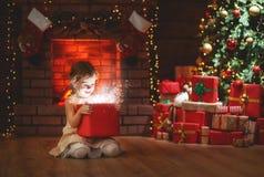 Child girl with magic gift on Christmas Eve. Child girl with magic gift sitting  in front of Christmas tree on Christmas Eve Royalty Free Stock Photos