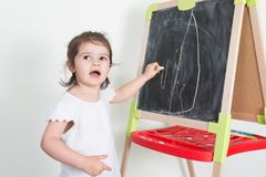 Child girl makes chalk drawings on a chalkboard. Toys royalty free stock photo