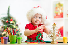 Child girl making christmas decorations with play clay toy Royalty Free Stock Photos