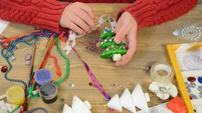 Child girl is making decoration for holidays. Crafts and toys, christmas tree and other. Painting watercolors. Top view. Artwork. Workplace with creative stock video footage