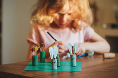 Child girl making easter craft tic tac toe game at home. Child girl making easter craft tic tac toe game with bunnies and flowers from cork at home Royalty Free Stock Images