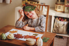 Child girl making herbarium at home, autumn seasonal crafts Stock Image
