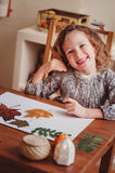 Child girl making herbarium at home, autumn seasonal crafts. Cute child girl making herbarium at home, autumn seasonal crafts royalty free stock photography