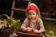 Child girl making rowan berry beads in autumn garden Royalty Free Stock Images