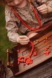 Child girl making rowan berry beads in autumn garden Royalty Free Stock Photo