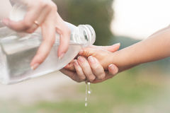 Child girl and mom washing hands with a bottle of clear water. Hygiene concept. Child girl and mom washing hands with a bottle of clear water on nature Stock Photo