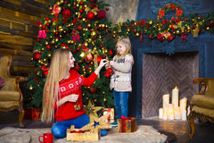 Child girl with mother decorating Christmas tree indoors Royalty Free Stock Photos