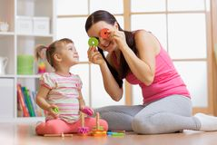 Child girl and mother have a fun playing together with puzzle toys Stock Images