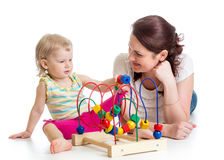 Child girl and mother play with color educational toy Stock Photos