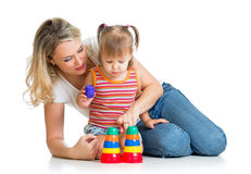 Child girl and mother play together with cup toys. Kid girl and mother playing together with cup toys Royalty Free Stock Photo