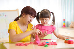 Child girl and mother playing with kinetic sand at home Royalty Free Stock Photography