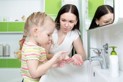 Child girl and mother washing hands with soap in bathroom Royalty Free Stock Photos